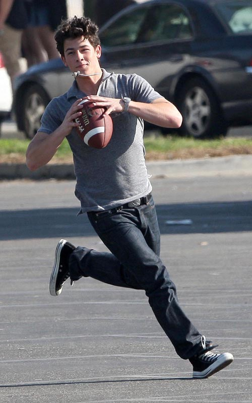 The Jonas Brothers Tossing A Football On Set