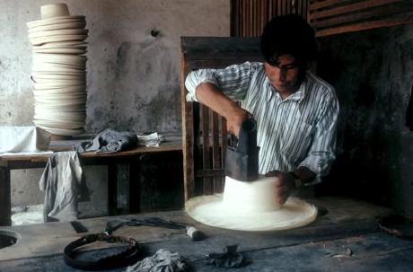 Empleando un hierro caliente, un joven artesano añade los toques